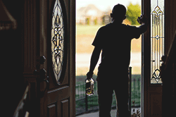 Man standing by open door with alcohol bottle in hand